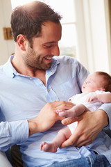 Father At Home With Newborn Baby Daughter