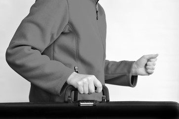 Hands of a woman carry travel suitcase