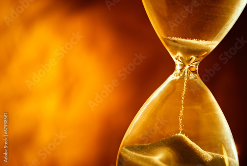 Sand passing through the bulbs of an hourglass - 67938561