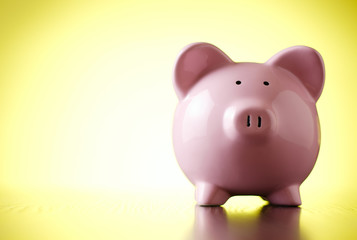 Pink piggy bank on a colorful yellow background