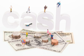 Miniature people sitting and standing  on cash wooden letters