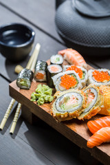 Fresh sushi on wooden board served with tea
