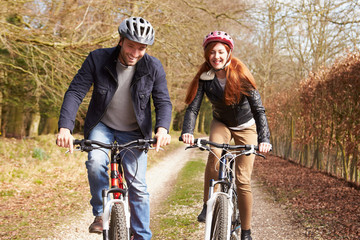 Couple On Cycle Ride In Winter Countryside