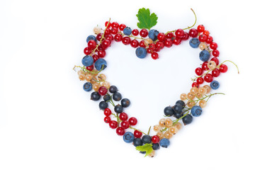 assorted garden berries in a heart-shaped, top view, isolated