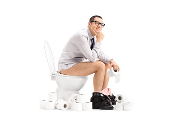 Peaceful young man sitting on a toilet