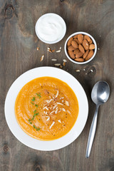 carrot soup with almonds and yogurt on the plate, top view