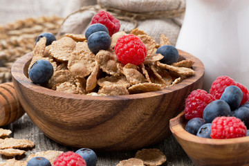 wholegrain flakes with berries in a wooden bowl, close-up