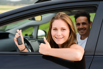 happy young couple driving new car on holiday trip in summer