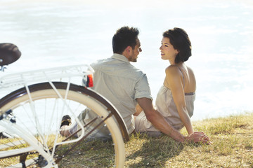 Couple with bicycle resting in front of the lake
