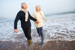 Leinwanddruck Bild - Senior Couple Walking Along Winter Beach