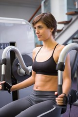 Focused brunette using weights machine for arms