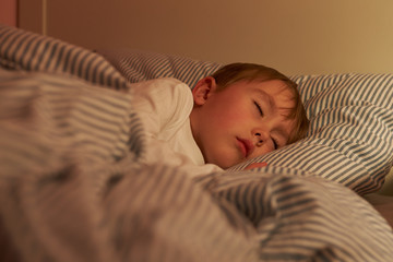 Young Boy Asleep In Bed At Night