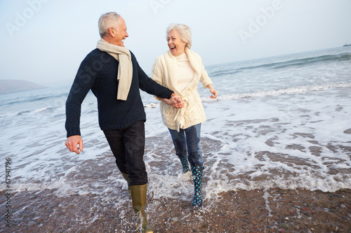 Senior Couple Walking Along Winter Beach - 67941796