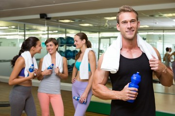 Fit man smiling at camera in busy fitness studio