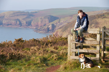 Boy With Dog Walking Along Coastal Path