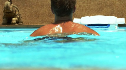 Man Swimming in Sunny Pool.