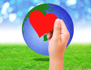 Blank red paper shape in hand and globe on grass background.