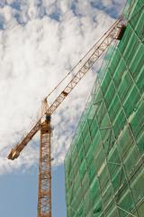 Ein grosser Baukran neben einem eingerüstetem Neubau
