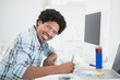 Young designer working at his desk smiling at camera