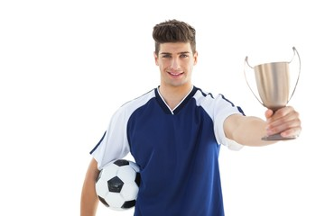 Football player in blue jersey holding winners cup