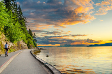 Sunset over The Seawall of Vancouver with cyclist in motion