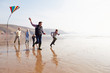 Multi Generation Family Flying Kite On Winter Beach - 67943700