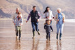 Multi Generation Family Running On Winter Beach - 67943935
