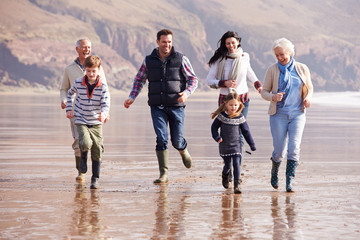 Multi Generation Family Running On Winter Beach