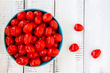 Fresh red cherry tomatoes on a wooden background