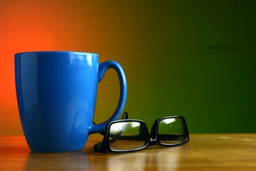 Blue coffee mug and eyeglasses