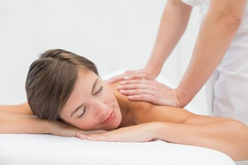 Attractive woman receiving shoulder massage at spa center