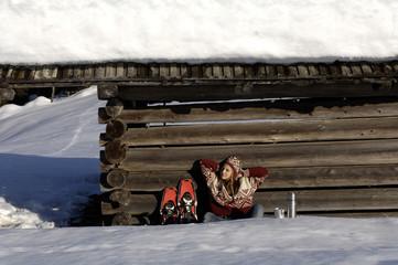 Frau entspannt vor der Hütte