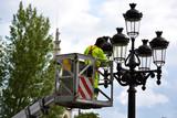 obrero pintando una farola de la calle