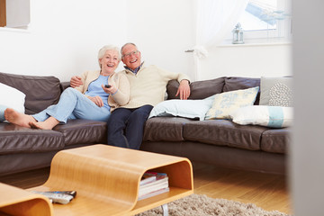 Senior Couple Sitting On Sofa Watching TV