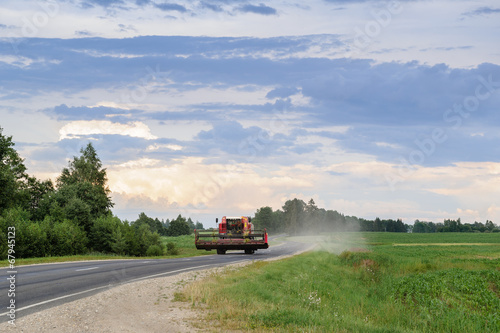 Combine tractor at the road in fields - 67945123