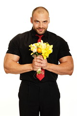 Big man in black shirt holds bouquet of flowers