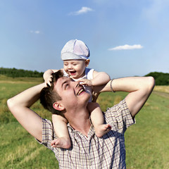 father holds a small child on his shoulders