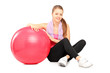 Young girl sitting next to a fitness ball