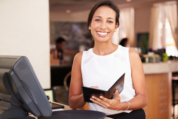 Portrait Of Waitress In Hotel Restaurant Preparing Bill