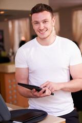 Portrait Of Waiter In Hotel Using Digital Tablet