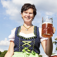 Woman in dirndl with beer mug at the Oktoberfest