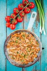 fried chanterelle mushrooms with green onions in a frying pan