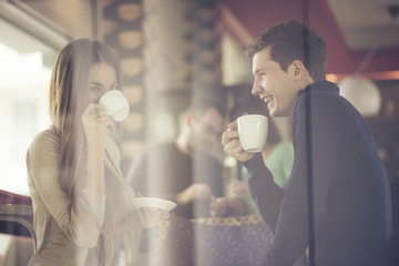 Two couples shot through window enjoying coffee