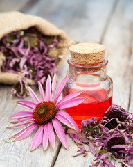 essential oil in glass bottle and coneflower on wooden rustic ta