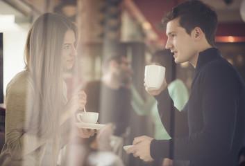 Two couples shot through window enjoying coffee