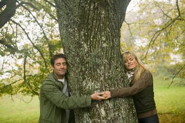 Paar lächelnd und umarmt Baum