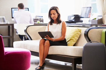 Businesswoman Working On Digital Tablet In Hotel Lobby