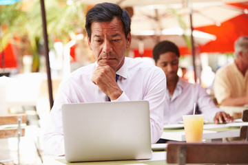 Businessman Working On Laptop In Outdoor Cafe