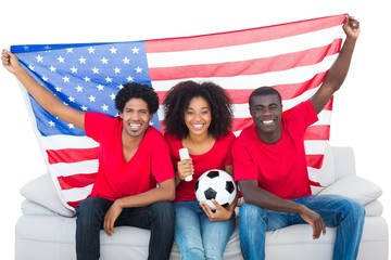 Happy football fans in red sitting on couch with usa flag