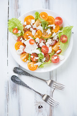 Vegetable salad with feta, white wooden background, above view